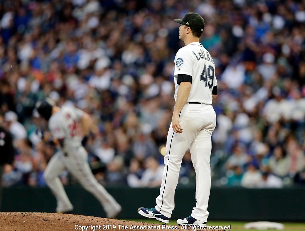Minnesota Twins' C.J. Cron rounds the bases after hitting a home run with Seattle Mariners pitcher Wade LeBlanc on the mound during a baseball game, Saturday, May 18, 2019, in Seattle. (AP Photo/John Froschauer)