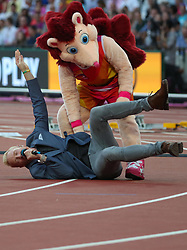 London, August 12 2017 . Hero the Hedgehog mischievously dumps Iwan Thomas on the ground on day nine of the IAAF London 2017 world Championships at the London Stadium. © Paul Davey.