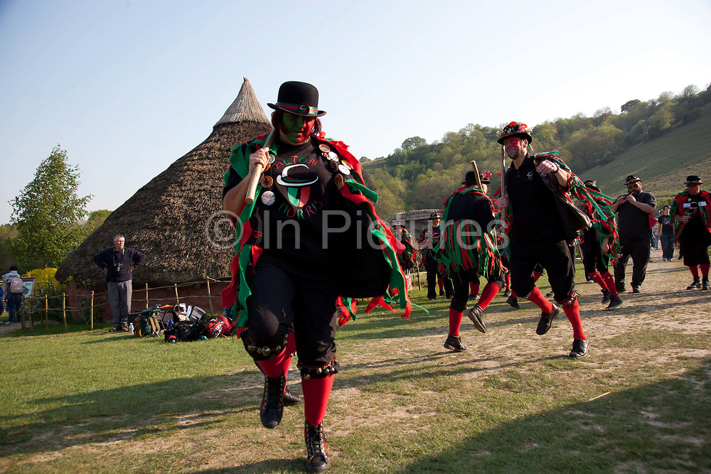 Morris dancers in traditional attire perform for crowds, visitors, english traditions. The annual Beltane celebrations at Butser ancient farm, Hampshire, marking the beginning of the British summer.