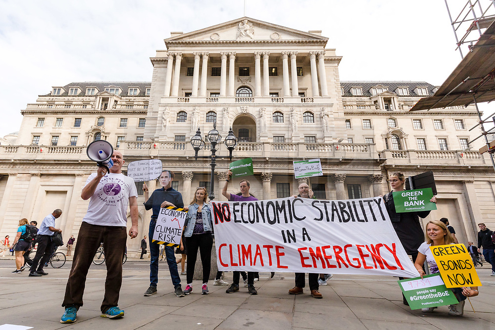 © Licensed to London News Pictures. 11/07/2019. London, UK.  Environment protesters stage a demonstration outside the Bank of England this morning to highlight the threat of climate breakdown to economic and financial stability and demand that Governer of the Bank of England, Mark Carney rules out asset purchases in high carbon sectors during quantitative easing, whilst favouring green projects . The Bank of England will release its latest Financial Stability Report today.  Photo credit: Vickie Flores/LNP