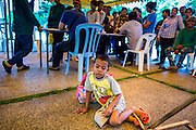 "17 JULY 2014 - BANGKOK, THAILAND: A Cambodian child waits for his parents to finish registering for temporary Thai ID cards at the temporary ""one stop service center"" in the Bangkok Youth Center in central Bangkok. Thai immigration officials have opened several temporary ""one stop service centers"" in Bangkok to register undocumented immigrants and issue them temporary ID cards and work permits. The temporary centers will be open until August 14.    PHOTO BY JACK KURTZ"