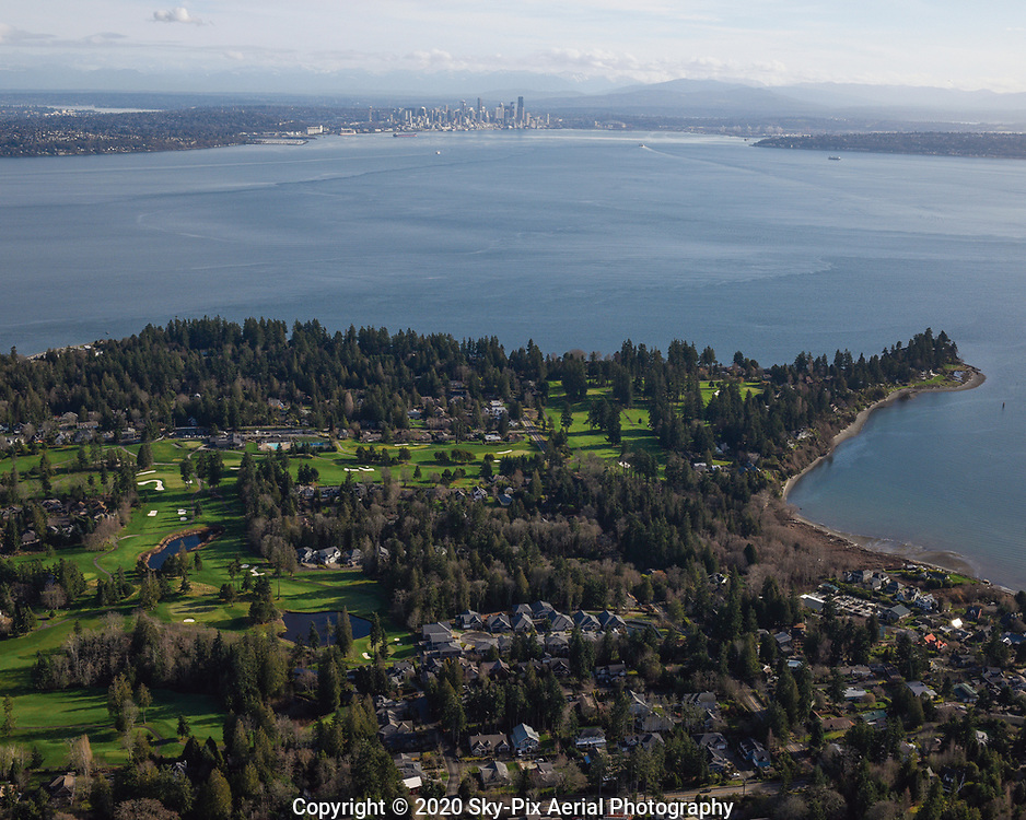 Scenic aerial view overlooking Wing Point Golf & Country Club, on Bainbridge Island, with Puget Sound, and Seattle in the background.