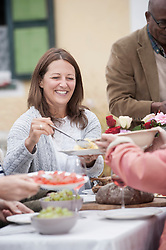Woman with family sharing food and serving each other