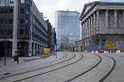 Tram lines in front of Town Hall in Birmingham city centre is virtually deserted due to the Coronavirus outbreak on 31st March 2020 in Birmingham, England, United Kingdom. Following government advice most people are staying at home leaving the streets quiet, empty and eerie. Coronavirus or Covid-19 is a new respiratory illness that has not previously been seen in humans. While much or Europe has been placed into lockdown, the UK government has announced more stringent rules as part of their long term strategy, and in particular social distancing.
