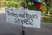 An activist from Extinction Rebellion holds an anti-HS2 banner on 26th June 2020 in Denham, United Kingdom. Activists from HS2 Rebellion and Extinction Rebellion UK are taking part in a 'Rebel Trail' hike along the route of the HS2 high-speed rail link in protest against its environmental impact and to question the viability of the £100bn+ project.