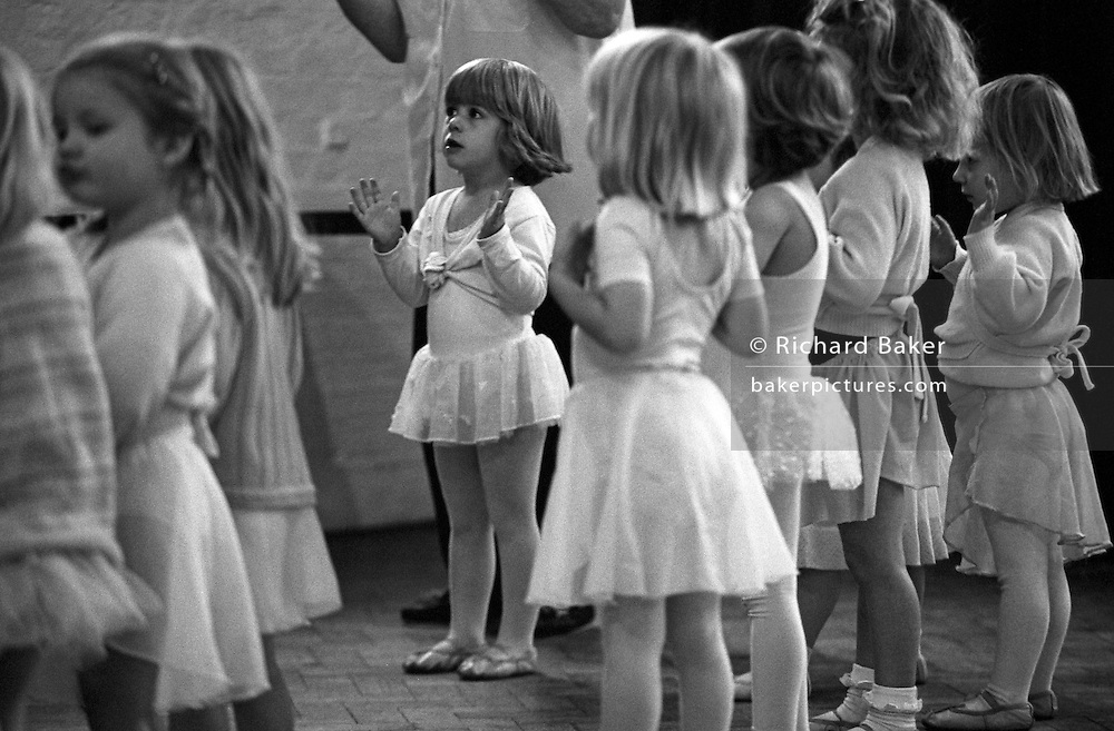 Three and four year-old girls clap their hands during a Saturday morning ballet dance group in south London.