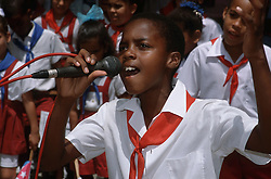 Young boy wearing uniform singing into microphone,