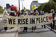 Extinction Rebellion 'Shell Out' protest 'We rise in peace' banner on 8th September 2020 in London, United Kingdom. The environmental group gathered outside the Shell building to protest at the ongoing extraction of fossil fuels and the resulting environmental record. Extinction Rebellion is a climate change group started in 2018 and has gained a huge following of people committed to peaceful protests. These protests are highlighting that the government is not doing enough to avoid catastrophic climate change and to demand the government take radical action to save the planet.