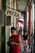 A man shuffles through his wallet as he prepares to pay for pizza on the street of Baracoa, Cuba on Monday July 14, 2008.