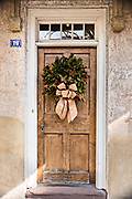 A wooden door of a historic home decorated with a Magnolia leaf Christmas wreath on Meeting Street in Charleston, SC.