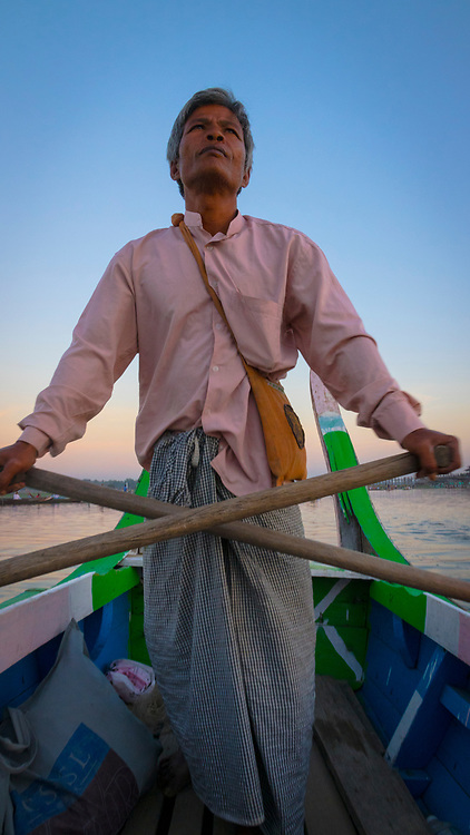 Boat guide in the Taungthaman Lake near Amarapura in Myanmar guiding tourists to the sunset at the U Bien Bridge