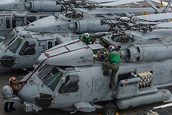 """WATERS SOUTH OF JAPAN (May 18, 2017) Sailors assigned to the """"Saberhawks"""" of Helicopter Maritime Strike Squadron (HSM) 77 inspect an MH-60R Sea Hawk helicopter on the flight deck of the aircraft carrier USS Ronald Reagan (CVN 76). The ship is the flagship of Carrier Strike Group 5, providing a combat-ready force that protects and defends the collective maritime interests of its allies and partners in the Indo-Asia-Pacific region. (U.S. Navy photo by Mass Communication Specialist 2nd Class Jamal McNeill/Released)170518-N-PF593-029 <br /> Join the conversation:<br /> http://www.navy.mil/viewGallery.asp<br /> http://www.facebook.com/USNavy<br /> http://www.twitter.com/USNavy<br /> http://navylive.dodlive.mil<br /> http://pinterest.com<br /> https://plus.google.com"""