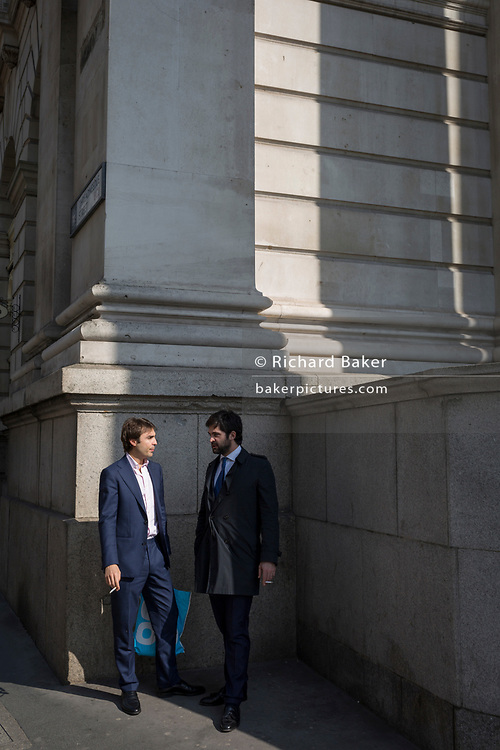 Two cigarette smokers talk at Royal Exchange on Threadneedle Street in the City of London, the capital's financial district also known as the Square Mile, on 6th April 2017, in London, England.