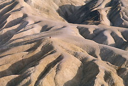 CA: Death Valley National Park Zabriskie Point with lone hiker    .Photo by Lee Foster, lee@fostertravel.com, www.fostertravel.com, (510) 549-2202.Image: cadeat201