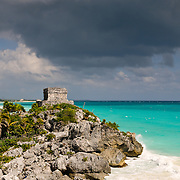 El Castillo, part of the Mayan ruins at Tulum, sits on an exposed, rocky outcrop with dark gray, ominous clouds in the distance. Tulum was a commercial port that traded extensively throughout Central America and Central Mexico. It is now a popular tourist destination, in party because it sits on beautiful Caribbean beaches.