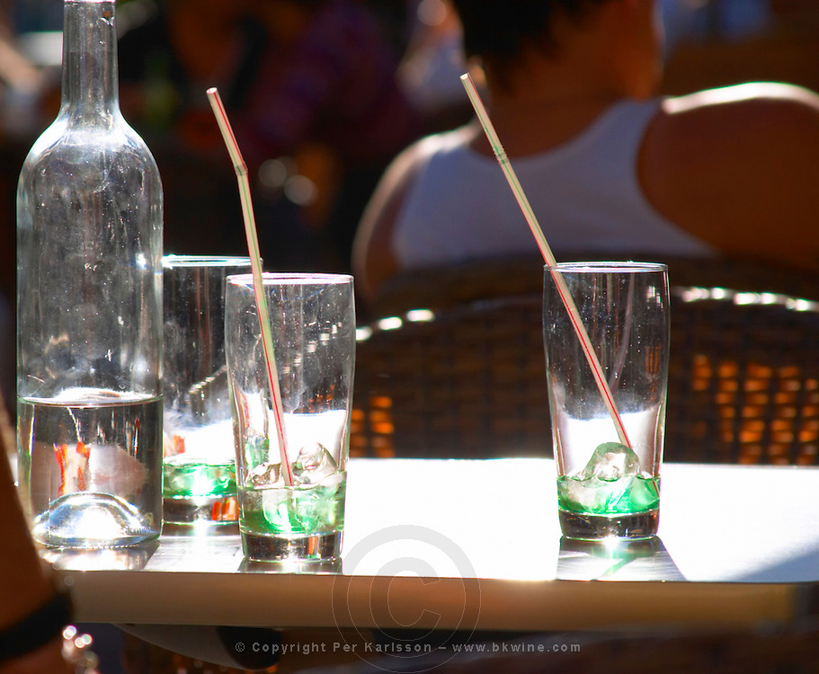 An outside cafe terrasse table in Bordeaux with empty glasses of green 'diabolo menthe' drink a bottle of water