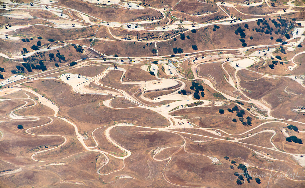From a distance, swirling shapes and contrasting colours resemble an oily slick on water, in this aerial of roads and landscape in the oilfields at San Ardo, California