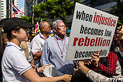 21 JANUARY 2014 - BANGKOK, THAILAND: SUTHEP THAUGSUBAN, reads a placard carried by a supporter during a march down Thanon Naradhiwas Rajanagarindra in the financial district of Bangkok. Suthep, the leader of the anti-government protests and the People's Democratic Reform Committee (PDRC), the umbrella organization of the protests, led a march through the financial district of Bangkok Tuesday. Shutdown Bangkok has entered its second week with no resolution in sight. Suthep is still demanding the caretaker government of Prime Minister Yingluck Shinawatra resign and the PM says she won't resign and intends to go ahead with the election.     PHOTO BY JACK KURTZ