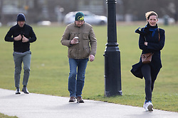 © Licensed to London News Pictures. 11/03/2021. London, UK. Members of the public walk on a windy Blackheath Common in South East London. A yellow weather warning for wind is in place in parts of the UK. Photo credit: George Cracknell Wright/LNP