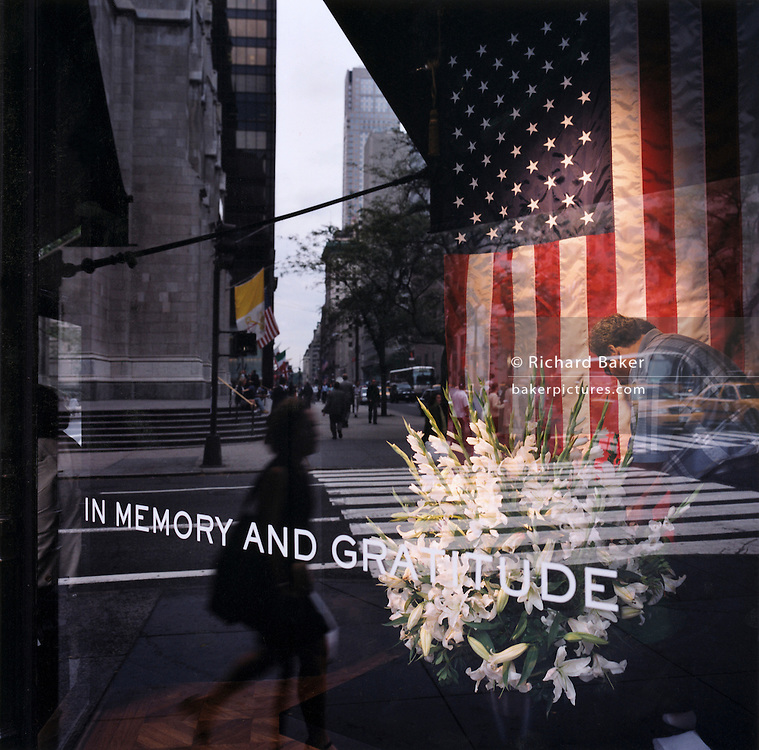 "Patriotic Americana - After 9/11.Attending a floral memorial in a 5th Avenue store front..In the week after the September 11th attacks, America sought to express their anger and patriotic unity. .As New Yorkers try to pick up the pieces of their lives in mid-town Manhatten , a worker carefully waters a floral memorial in the window of a 5th Avenue store window. New York City. ""Don't waste time in mourning. Organize!"" - From a New York poster."