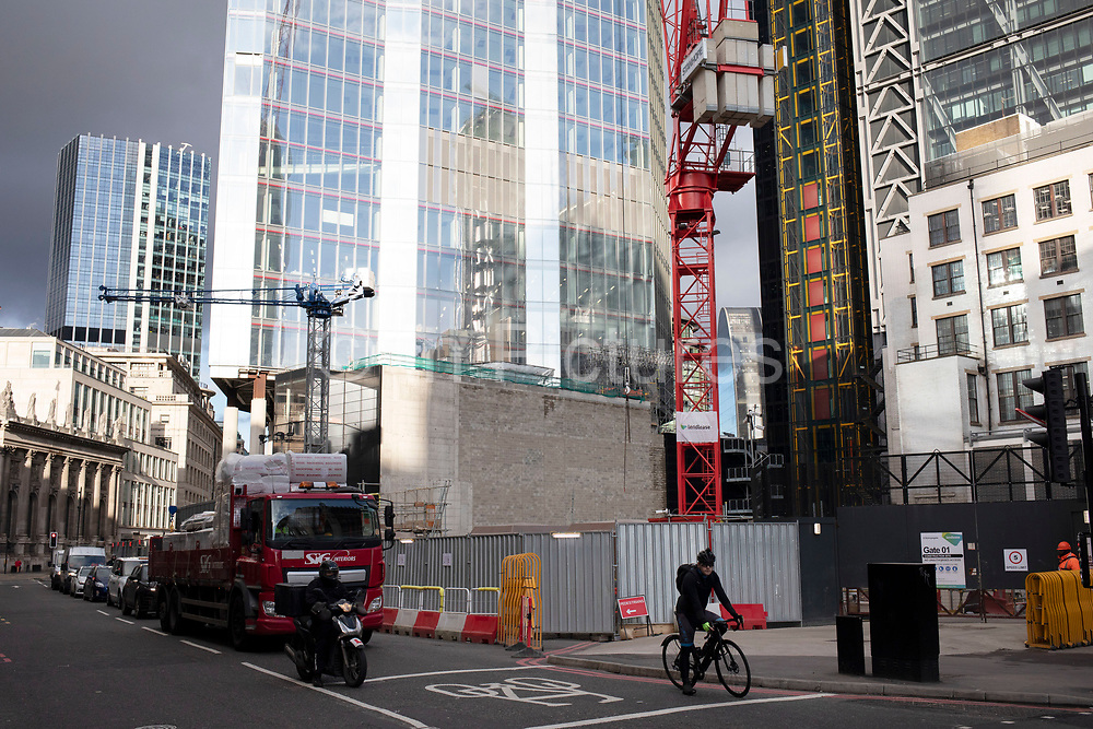 Street scene with traffic passing another construction site for the latest skyscraper in the City of London on 28th January 2020 in London, England, United Kingdom. The City of London is a historic financial district, home to both the great banking buildings. Modern corporate skyscrapers tower above the vestiges of medieval alleyways below.