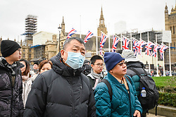 © Licensed to London News Pictures. 31/01/2020. LONDON, UK.  A tourists from China wears a facemask as they walk through Parliament Square.  It has been reported that Chief Medical Officer Professor Chris Whitty has confirmed that two people in England have tested positive for the coronavirus.  Photo credit: Stephen Chung/LNP