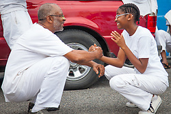 Donovan Berry, left, with daughter Na'im perform an opening sequence in Capoeira, a Brazilian martial arts form created by African descendents.  10th Annual Dollar Fo' Dollar Culture & History Tour commemorating the anniversary of the successful protest  demanding better pay by Queen Coziah and the 19th century coal laborers in the streets of downtown Charlotte Amalie.  12 September 2015.  St. Thomas, VI.  © Aisha-Zakiya Boyd10th Annual Dollar Fo' Dollar Culture & History Tour commemorating the anniversary of the successful protest  demanding better pay by Queen Coziah and the 19th century coal laborers in the streets of downtown Charlotte Amalie.  12 September 2015.  St. Thomas, VI.  © Aisha-Zakiya Boyd