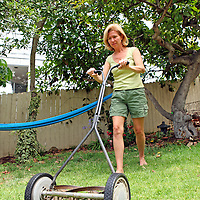 A woman mows the grass with an environmentally-friendly push reel mower.