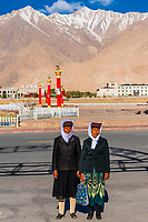 Tajik women with the Pamir Mountains behind, Tashkurgan (means Stone Fortress in Uyghur), at 10,100 feet, along the Karakoram Highway. It was a caravan stop on the Silk Road and all routes of the Silk Road converged here to journey southward to Pakistan. It sits on the borders of both Afghanistan and Tajikistan, and is close to the border of Kyrgyzstan and Pakistan.  The majority population in the town are ethnic Mountain Tajiks. Xinjiang Province, China.