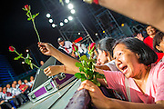 01 MARCH 2013 - BANGKOK, THAILAND: .A Thai woman tries to hand roses to NATTAWUT SAI-KUA (not in picture) during the last election rally Pongsapat Pongchareon who is running for governor of Bangkok Nattuwat is a popular Red Shirt leader and member of Thai Parliament from the Pheu Thai party. The election is Sunday, March 3 and no campaigning is allowed 24 hours before election day. Police General Pongsapat Pongcharoen (retired), a former deputy national police chief who also served as secretary-general of the Narcotics Control Board is the Pheu Thai Party candidate in the upcoming Bangkok governor's election. He resigned from the police force to run for Governor. Former Prime Minister Thaksin Shinawatra reportedly personally recruited Pongsapat. Most of Thailand's reputable polls have reported that Pongsapat is leading in the race and likely to defeat Sukhumbhand Paribatra, the Thai Democrats' candidate and incumbent. The loss of Bangkok would be a serious blow to the Democrats, whose national base has been the Bangkok area.    PHOTO BY JACK KURTZ