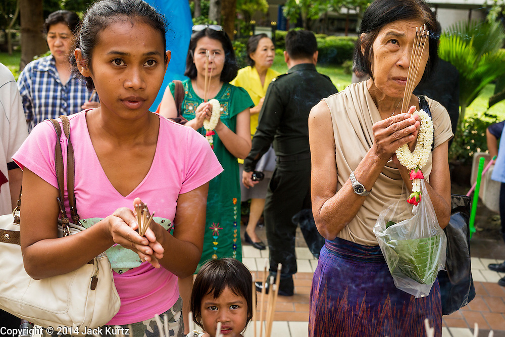 09 OCTOBER 2014 - BANGKOK, THAILAND: Women pray for Bhumibol Adulyadej, the King of Thailand in the courtyard at Siriraj Hospital. The King has been hospitalized at Siriraj Hospital since Oct. 4 and underwent emergency gall bladder removal surgery Oct. 5. The King is also known as Rama IX, because he is the ninth monarch of the Chakri Dynasty. He has reigned since June 9, 1946 and is the world's longest-serving current head of state and the longest-reigning monarch in Thai history, serving for more than 68 years. He is revered by the Thai people and anytime he goes into the hospital thousands of people come to the hospital to sign get well cards.   PHOTO BY JACK KURTZ