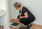 Dietitian calibrates her analogue scale before weighing a anorectic patient. the scale resolution should be no better than 0.5 Kg (1 pound) as this can be caused by liquid consumption and other physiological changes. Anorectic patients should be weighed with their back to the dial as they are very weight conscience and pay attention to every minor fluctuation in their weight