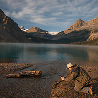 A photographer shoots beside a small inlet into  Bow Lake in Banff National Park, Alberta, Canada.
