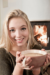 Young pretty blond teenage girl drinking coffee fire