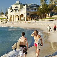 Couple walking with surfboards at Cottesloe Main Beach with Indiana Tearooms in the background