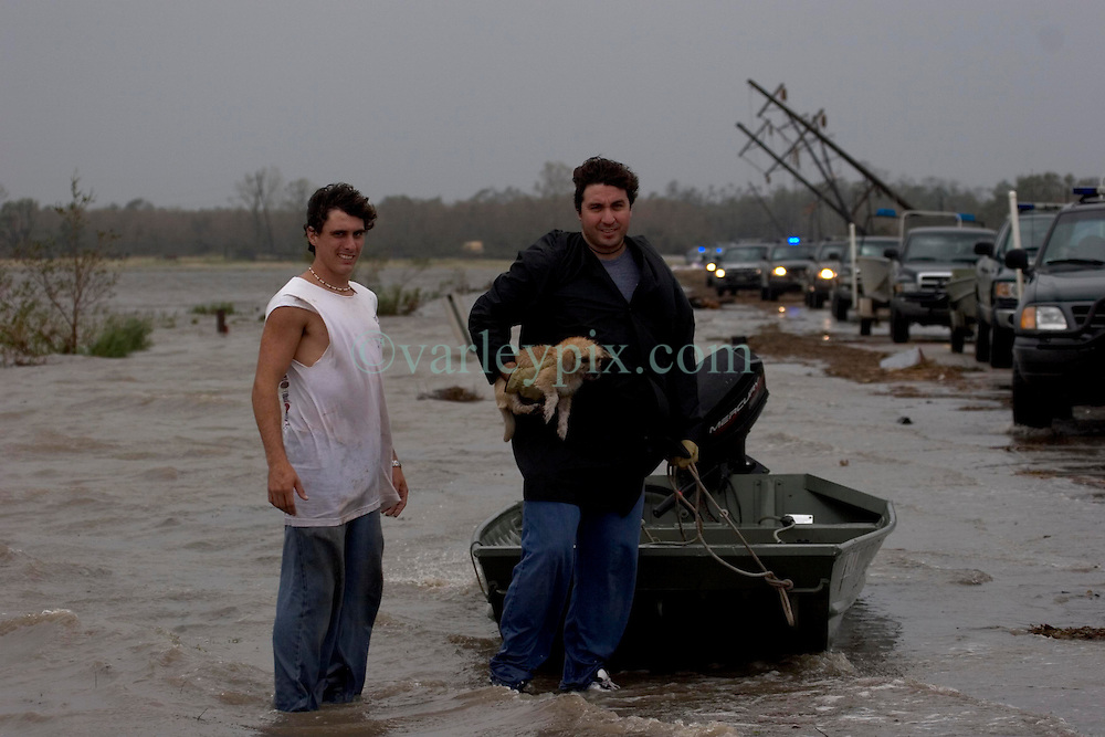 24th Sept, 2005. Hurricane Rita, rte 27, Louisiana where the storm hit hardest on the Louisiana/Texas border. The back edge of Rita floods across the roadway as rescue workers attempt to reach stranded flood victims. L/R Josh Herman and his uncle Romeo Espinosa try to get to their flooded convenience store in Carlyss with an abandoned puupy they rescued and named Rita.