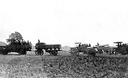 French military motorised vehicles carrying gun crews and a hauling field artillery, c1914.