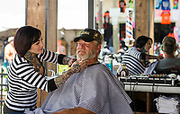 """Heather Manto of Austin TX gives Clay """"Mudd"""" Carroll a beard trim and shave at Flo's Chop Shop on Lakeside Avenue in the Progressive Insurance booth.  (Karen Bobotas/for the Laconia Daily Sun)"""