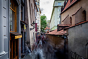 """A guided tourist group is moving through """"Cervena"""" street passing the Old New Synagogue (Staronová synagoga) which is located on the right in """"Josefov"""", the Jewish Quarter in Prague."""