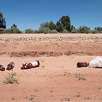 An empty beer bottles and a trash bag lay on the side of the road along Indian Rte 930 in St Michaels, AZ.