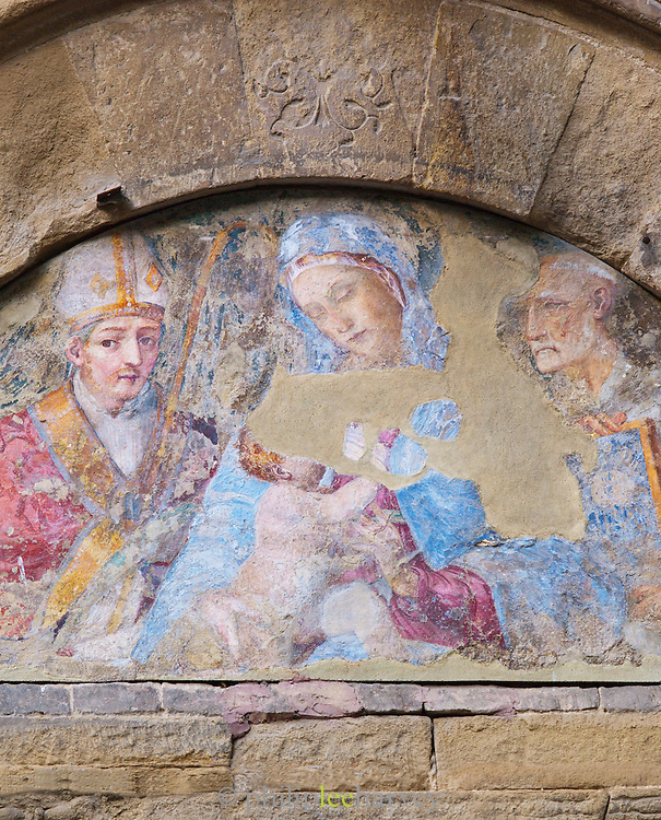 An old fresco, depiciting a religious catholic scene of the Virgin Mary and Jesus, seen near the Piazza del Campo in Siena, Tuscany, Italy