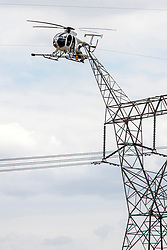 A repairman perches on a platform attached to a helicopter to work on a wire attached to a high voltage tower.