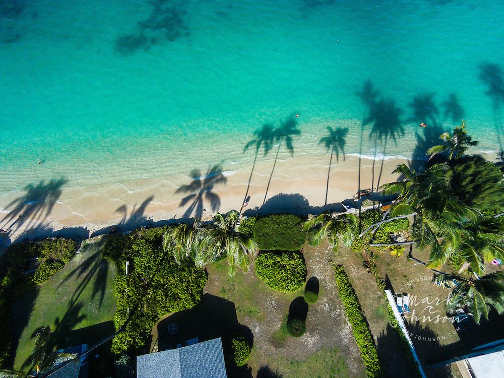An aerial photograph of the late afternoon sun casting palm treeshadows onto Lanikai Beach, Oahu, Hawaii