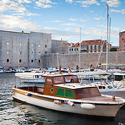 """Personal boats docked in the old port (harbor) of the old city of Dubrovnik, Croatia. St. John's Fortress can been seen in the background. <br /> <br /> Dubrovnik serves as the official setting of """"King's Landing"""" from the popular TV show """"Game of Thrones""""."""