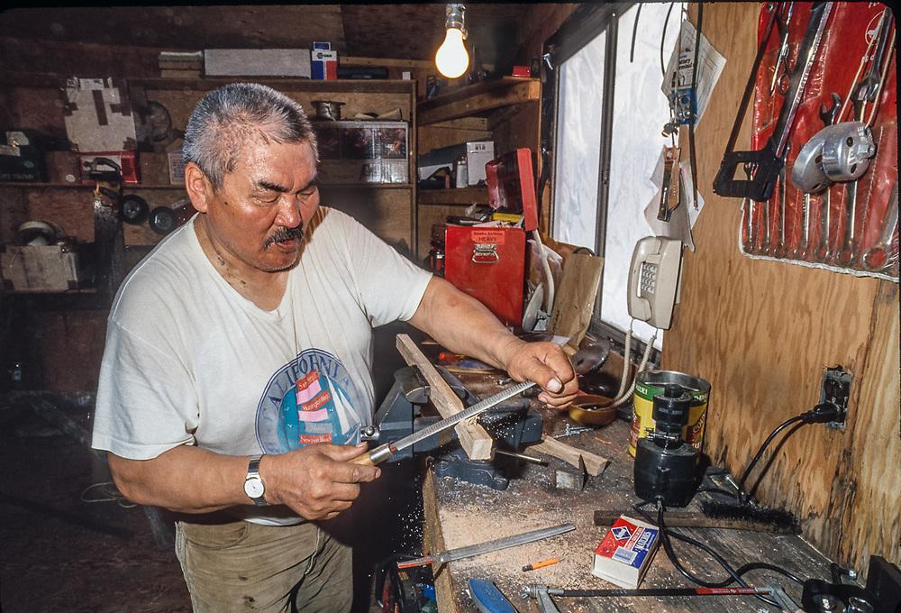 Don Smith files a wooden part for a cargo sled, Don's Sled Shop, Kobuk River Valley, Kiana, Alaska, USA