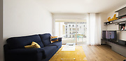 Living room with blue sofa, yellow carpet and bright window. Nobody inside