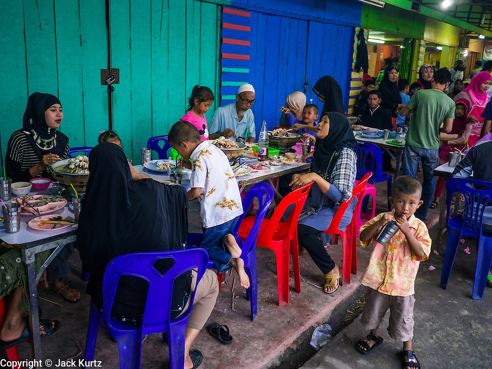 08 JULY 2013 - PATTANI, PATTANI, THAILAND:   A busy street side restaurant in Pattani Monday afternoon, the day before Ramadan. Ramadan starts July 9 and Monday was the last day observant Muslims were able to eat and drink during daylight hours. Muslims fast during the holy month of Ramadan, taking breakfast before dawn and not eating again until after sunset. The restaurants in Pattani, a Muslim majority city in southern Thailand, were packed Monday afternoon and evening.  PHOTO BY JACK KURTZ