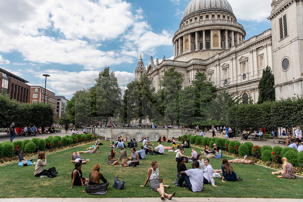 © Licensed to London News Pictures. 23/07/2018. London, UK. Office workers enjoy the sunshine at lunchtime outside St Paul's Cathedral as hot weather continues in the capital. Forecasters are predicting record temperatures this week. Photo credit: Rob Pinney/LNP