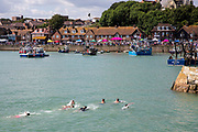 Young kids swim in the sea across the mouth of Folkstone Harbour after the annual Trawler race and fun day in Folkestone, Kent, England, United Kingdom.