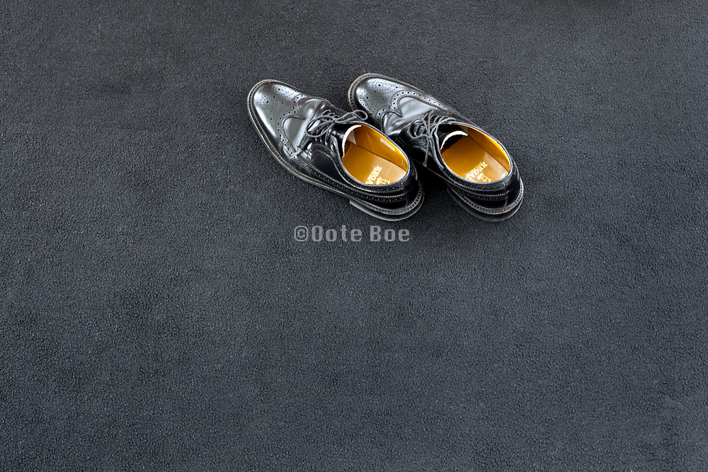 shiny black business shoes on a dark carpet